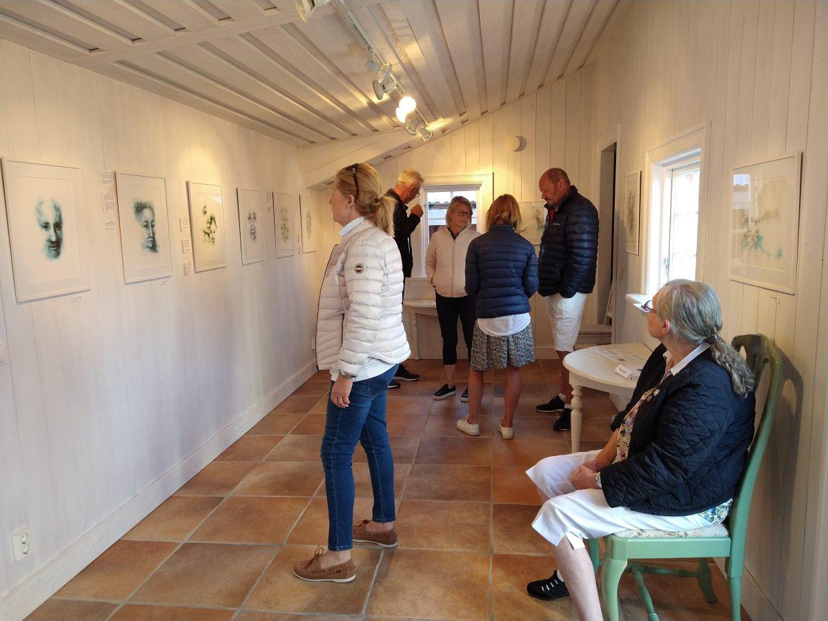 Besökare tittar på tavlor i ett galleri